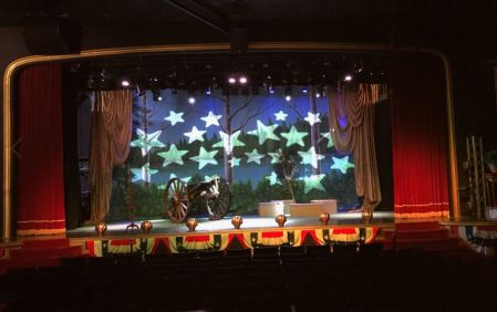 buttonwod civil war stage picture featuring a civil war cannon and a backdrop of a forest with stars overlaying the trees.