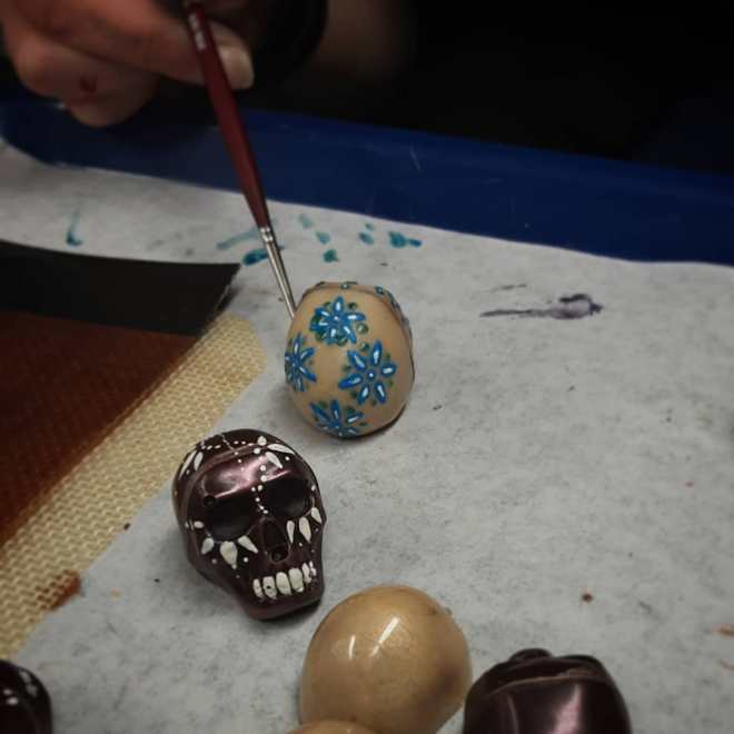 Rachel's painting THE DEAD: spicy caramel skulls. One is heirloom chile caramel in cinnamon-infused housemade white chocolate, while the other is dark ancho chile caramel. #chocolatier #diadelosmuertos #painting #chocolateasart