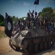 A screengrab taken on November 9, 2014 from a new Boko Haram video released by the Nigerian Islamist extremist group Boko Haram and obtained by AFP shows Boko Haram fighters parading on a tank in an unidentified town. The leader of the Nigerian Islamist extremist group Boko Haram, Abubakar Shekau, dismissed again government claims about ceasefire talks and threatened to kill the man who has presented himself as Boko HaramТs negotiator.  AFP PHOTO / HO / BOKO HARAM  = RESTRICTED TO EDITORIAL USE - MANDATORY CREDIT