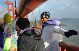 """June Solomon stretches her arms over the edge of the Golden Gate Bridge in San Francisco, Ca. on Friday, January 20, 2016 during a """"Bridge Together"""" demonstration. The event was coordinated by Satoriteller, a San Francisco art-based production studio to take place at the same time as the inauguration of President-elect Donald Trump to raise awareness for bullying and to take a stand against bullying rhetoric nationwide. Photo by David Andrews and is Property of Hoodline and Pixel Labs, Inc. Photo by David Andrews."""
