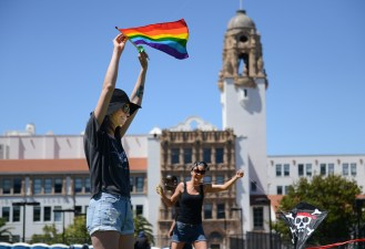 Krystal Barovetto, left, and her sister Dariann fly kites in front of Mission High School at Dolores Park in San Francisco, Ca. Krystal said they bought and were flying the rainbow flag in memory of a friend who recently passed.