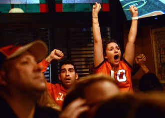 Meghan Shoemaker, right, and Justin Salerian prematurely celebrate what they what they thought was a Clemson touchdown at O'Sullivan's Irish Pub in Arlington, Va. during the NCAA Football National Championship game between the Clemson Tigers and the Alabama Crimson Tide on Monday, January 11, 2016. Shoemaker, a Clemson alumna from '08, joined other Clemson fans and alumni at the Irish Pub to to cheer on their Tigers, but Clemson fell to Alabama by a score of 45-40. Photo by David Andrews.