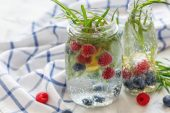 sparkling water with fruit on white towel