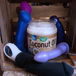Coconut Oil and Silicone Sex Toys - A jar of coconut oil is surrounded by various silicone sex toys