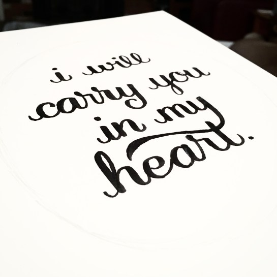"An angled photo of the words ""I will carry you in my heart"" written in a brush script."