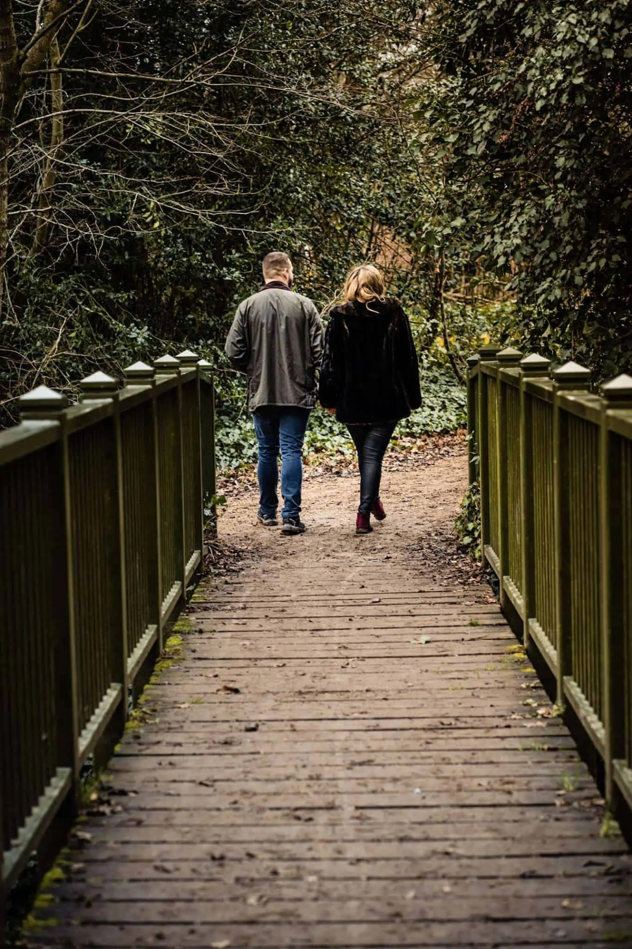 An engaged couple walking across a bridge in a north London park