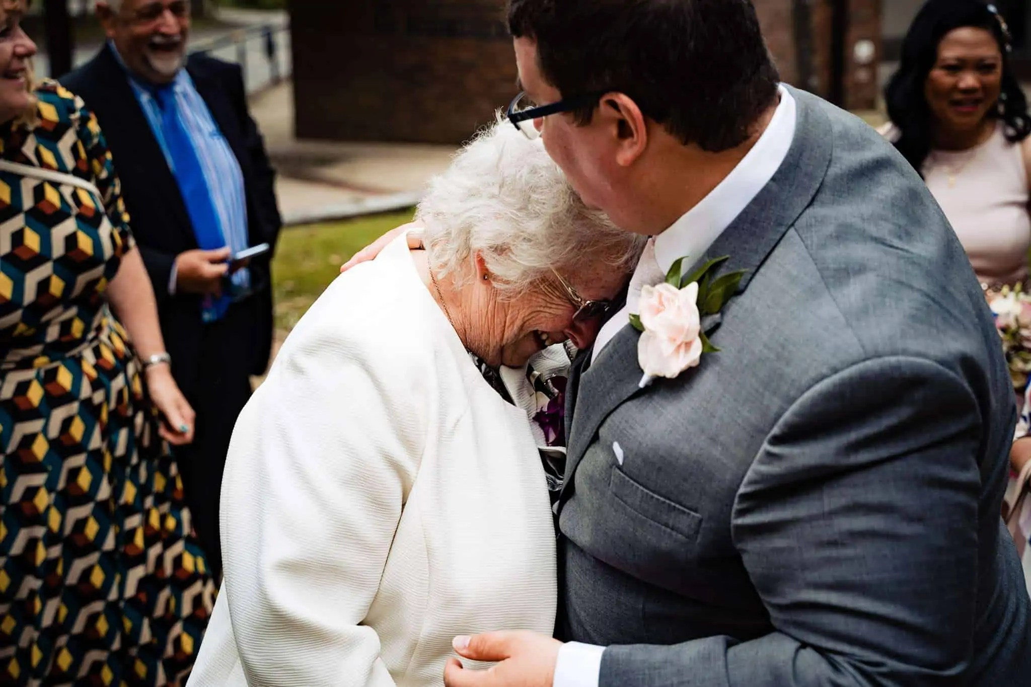 A groom and his mum sharing a tender hug after he has got married