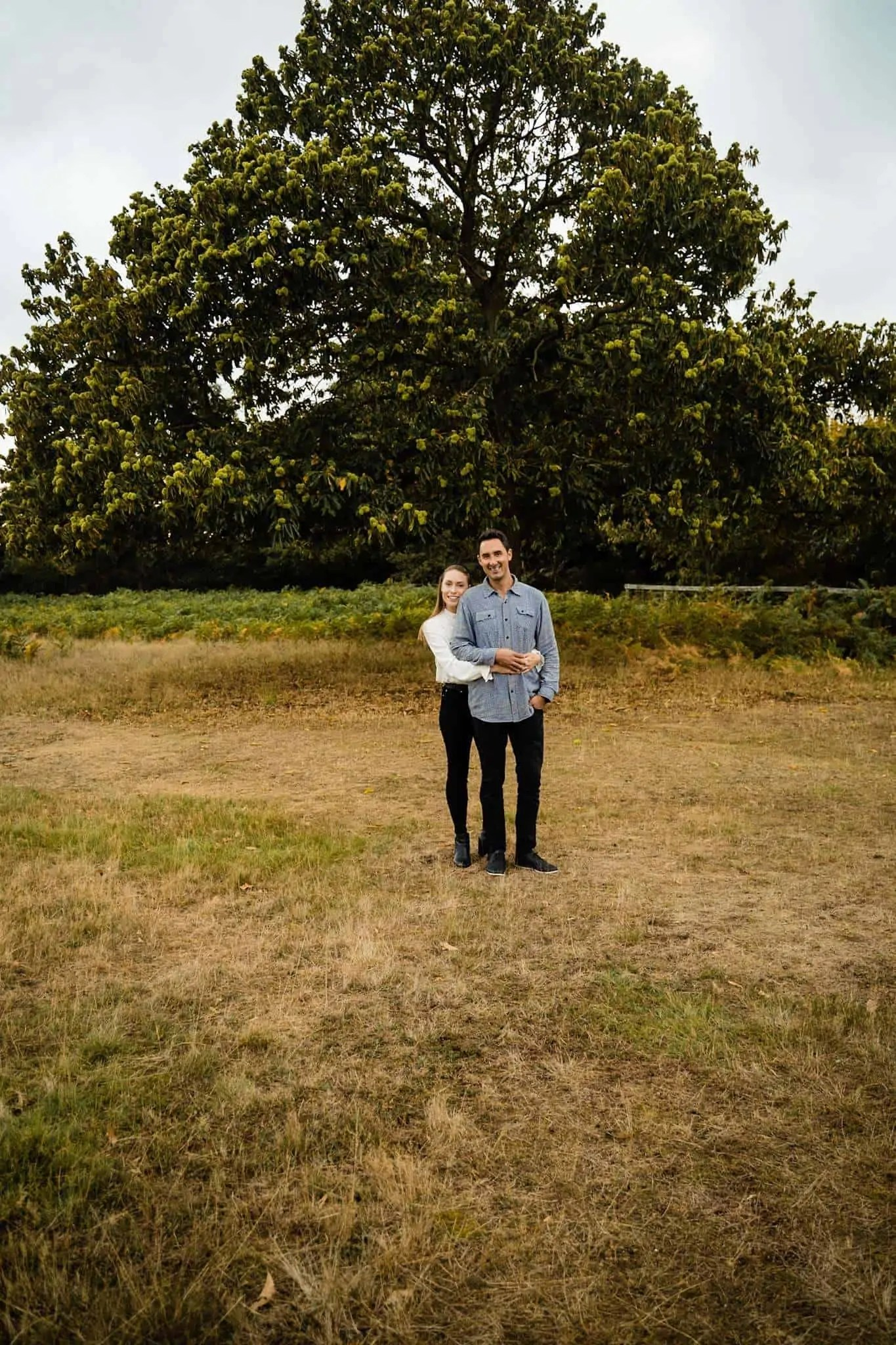 An engaged couple look at the camera during an engagement shoot in Richmond Park