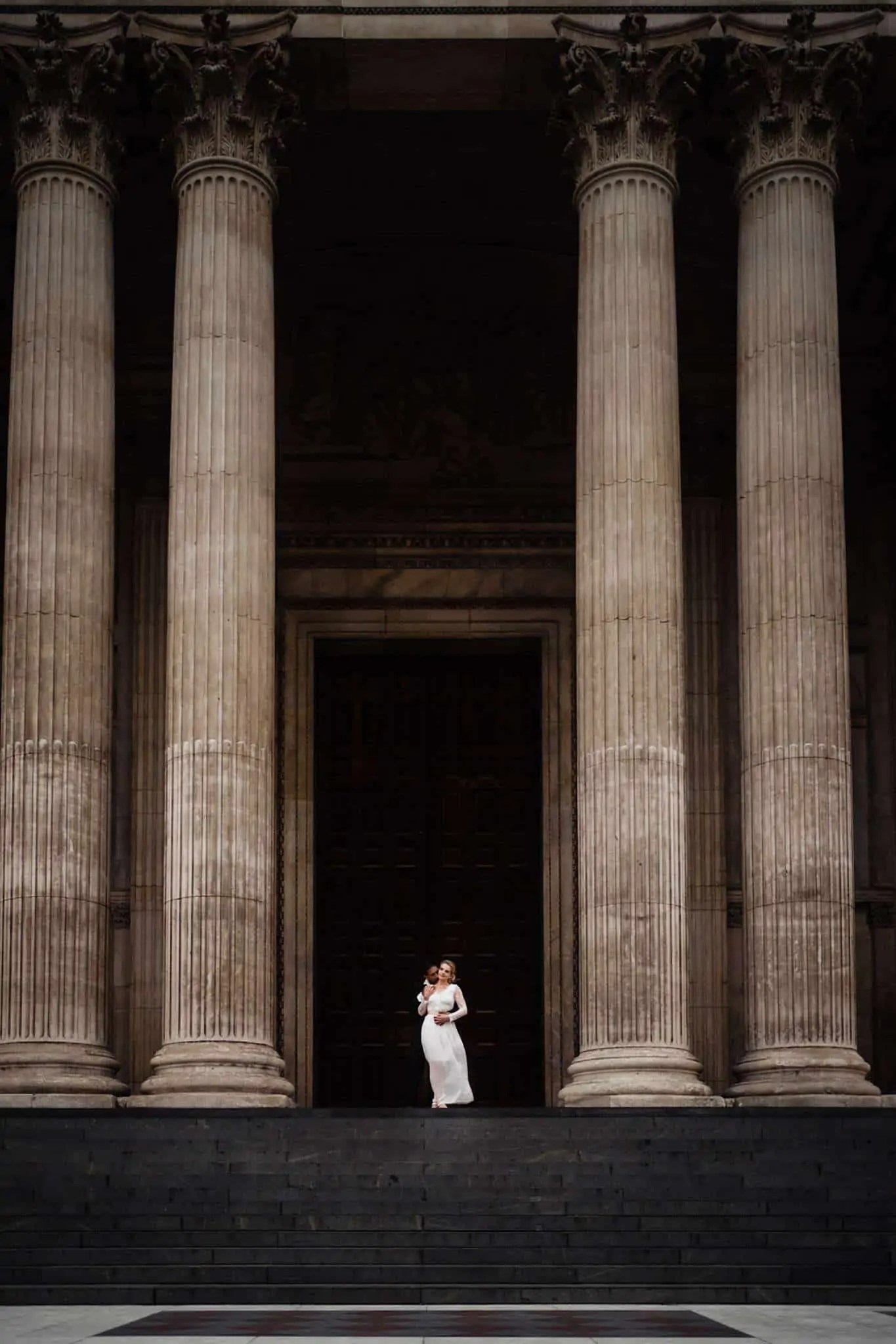 A bride and groom pose in front of St Paul's Cathedral, London during their couple portraits