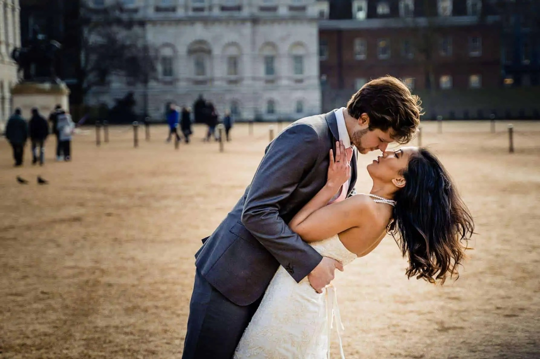 A newly engaged couple share a kiss in Horse Guards Parade, London
