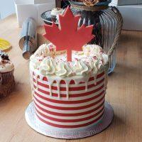 Gâteau ligné blanc et rouge avec coulis au chocolat blanc et feuille de maple sur le top canada