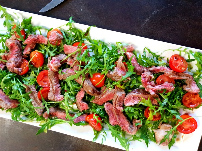 thinly sliced underdone steak with rocket salad