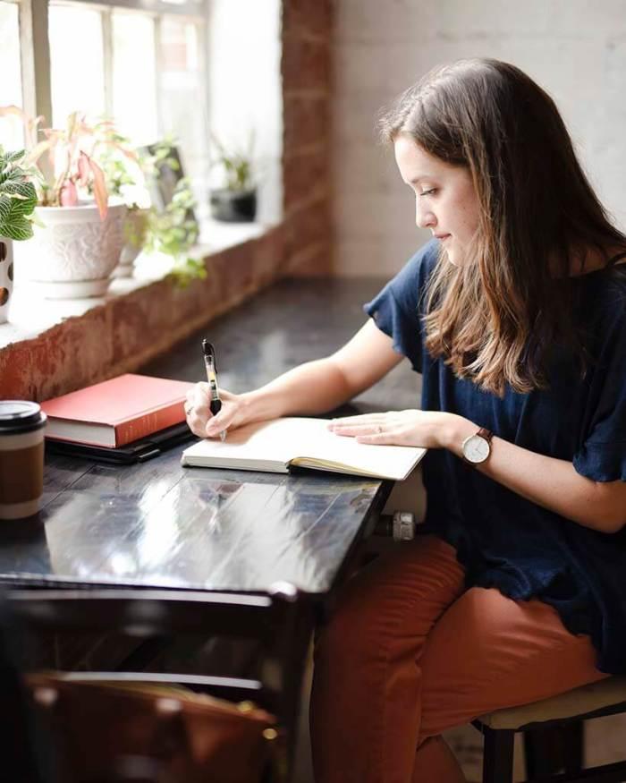 mulher escrevendo num caderno