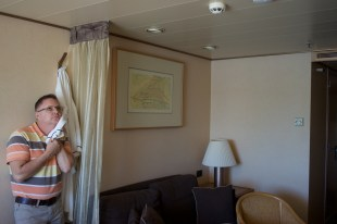 Andy feeling the luxurious bathrobe in our stateroom on the HAL Veendam