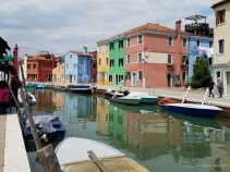 Brightly colored homes reflect in a canal in Burano