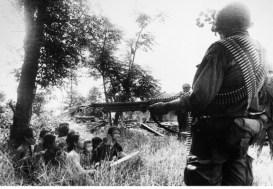 VIETNAM WAR: GUARD. An American machine gunner stands guard over women and children, while his comrades search a building near Saigon, 1969.