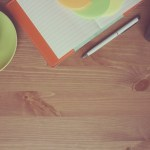 Image of coffee, notebook, plant on a wooden table