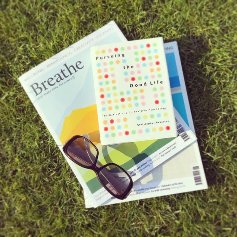 Breathe magazine good life book gucci sunglasses reading on lawn
