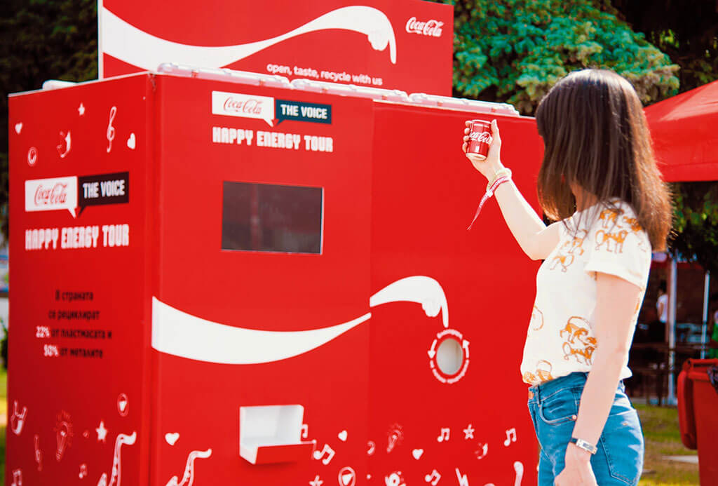 Coke logo points to recycling bins