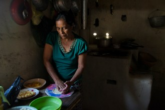 Bertha Maria López flattens masa to make tortillas for breakfast on the morning of March 10, 2015 in Sabana Grande, Nicaragua. She cooks the tortillas on the improved cookstove in her home, which decreases smoke and was built by the nongovernmental organization Grupo Fénix. Danika Worthington/JMC 470