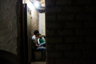 Juan Eliezer Alvarado and his cousin, Ricardo Felipe Perez, sit together talking on the night of March 9, 2015 in Sabana Grande, Nicaragua. They are able to stay up later with the light provided by the solar panel on the home installed by nongovernmental organization Grupo Fénix. Danika Worthington/JMC 470