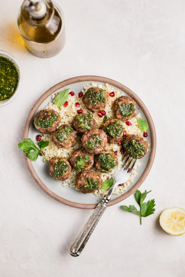 overhead shot of plate of garlic meatballs topped with chimichurri with a bowl of sauce and bottle of olive oil.