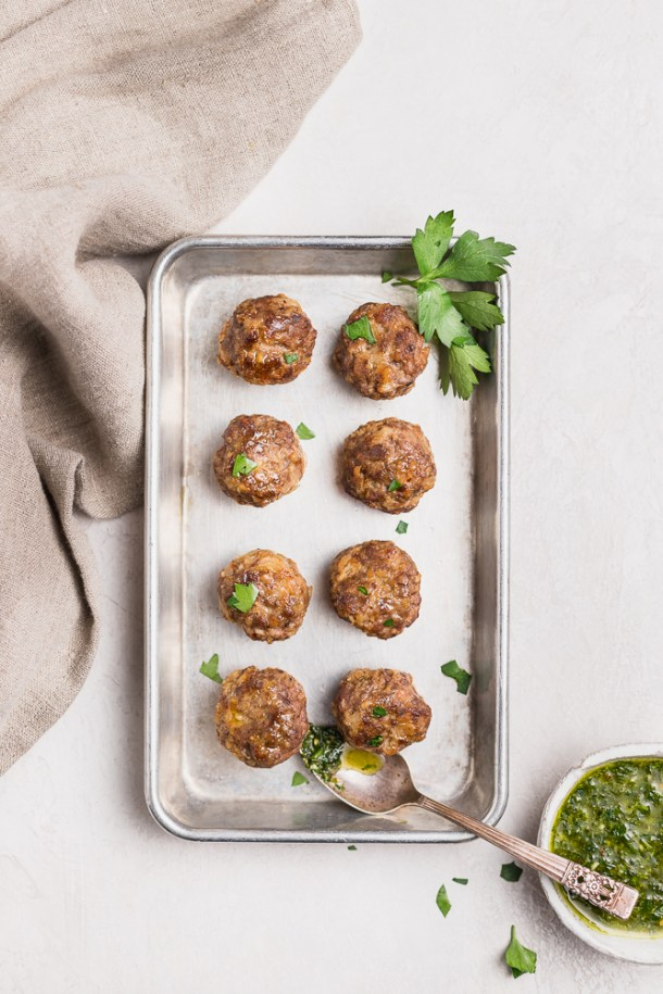 Tray of garlic meatballs with bowl of chimichurri.
