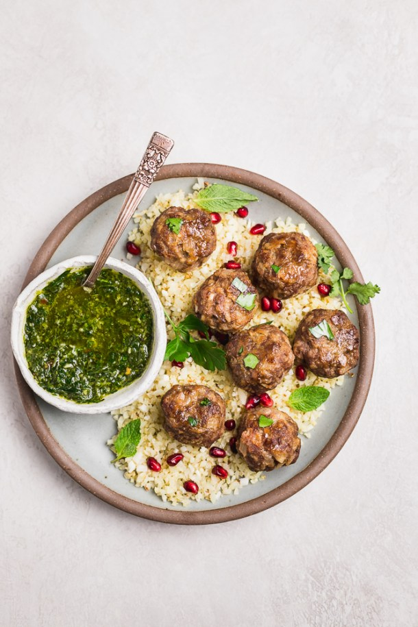 Plate of garlic meatballs with bowl of chimichurri.