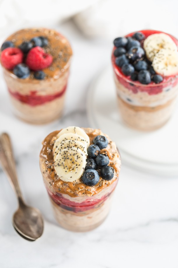 Up close overhead shots of overnight oats flavored with almond butter and date syrup and topped with raspberry jam and fruit.