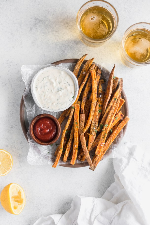 Overheadshot of baked sweet potato fries with ranch dipping sauce and cold beer.