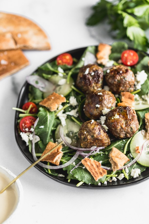 A kale salad with greek seasoned beef meatballs, pita croutons, feta, tomatoes, cucumbers, and onions with a side of lemon tahini dressing.
