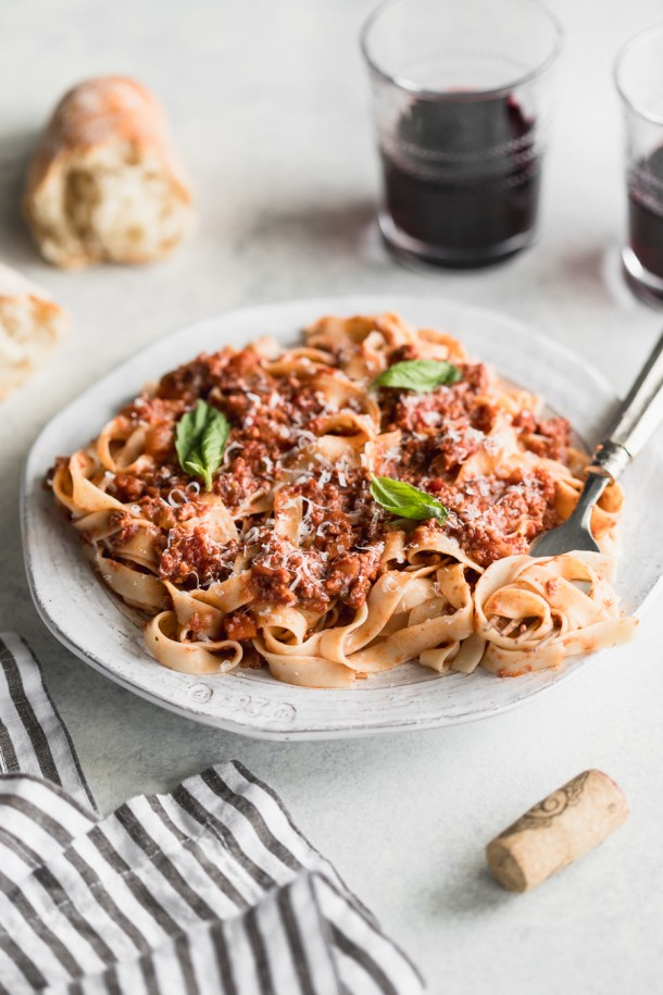 Side view of gluten-free pasta topped with a healthy meat sauce with 2 glasses of wine and french  bread.