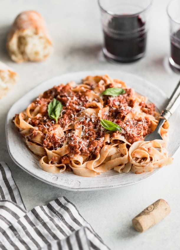 Side view of gluten-free pasta topped with a healthy meat sauce and paired with French bread and red wine.