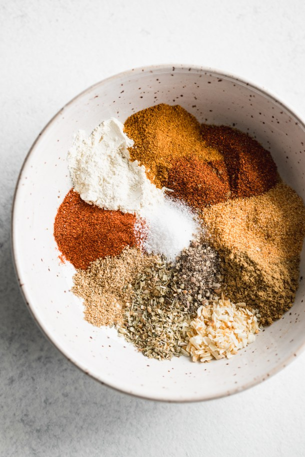 A close up of a bowl of a spice blend of chili powder, cumin, garlic powder, onion powder, dried oregano, smoked paprika, dried coriander, and salt and pepper.