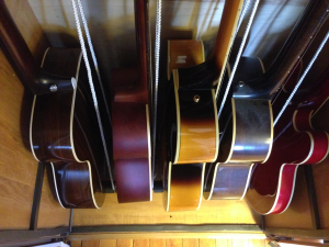 Guitar cabinet interior is 27.5 inches wide. I can fit 4 acoustic or archtop guitars plus one thinline guitar.