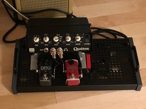 Quilter amp mounted to pedalboard by aluminum angle brackets.