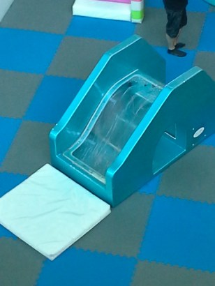 This is a slide which has a waterfall of water running under the slide surface. It´s in an arcade designed for two year olds.