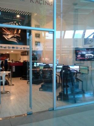 An arcade where kids were driving race car simulators on computers.