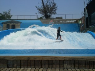 This is surfing in a mall. You pay some money and then ride the wave. It seemed to be powered by a dieasel motor. Santiago