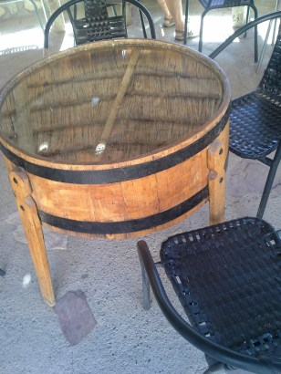 A table made from a wine cask. A piece of glass is on top. Under the glass there is a surface made of woven grass which holds various artifacts of interest.