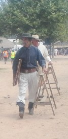 Two gauchos carrying their horses, saw-horses that is. (Dan humor)