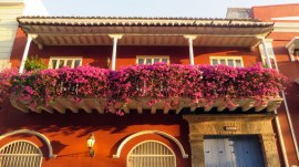 Colorful house with even more colorful flowers on the balcony in Cartagena