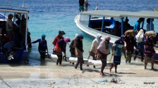 Women unloading building materials from boats. Note that they use scarves to hold the log. Gili Trawangan Island