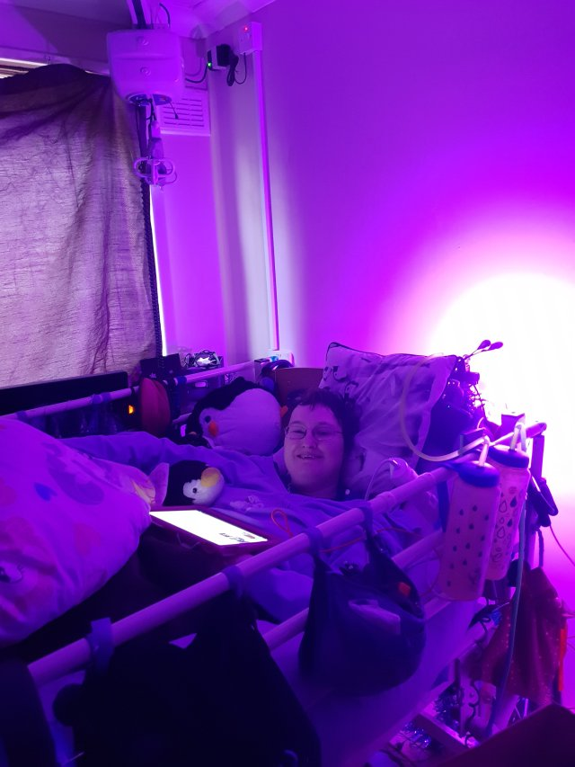 Danni is lying in bed in their back. They are smiling. The image is tinted purple from a light behind the bed.