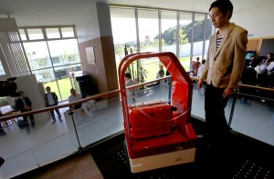 "A porter robot escort a hotel staff during a demonstration for media at Robot hotel ""Henn na Hotel"" in Sasebo, western Japan, Wednesday, July 15, 2015. (AP Photo/Shizuo Kambayashi)"