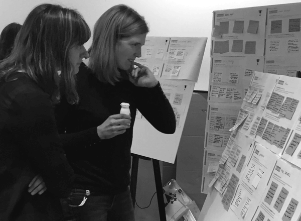 Two people looking and talking at a board of post its