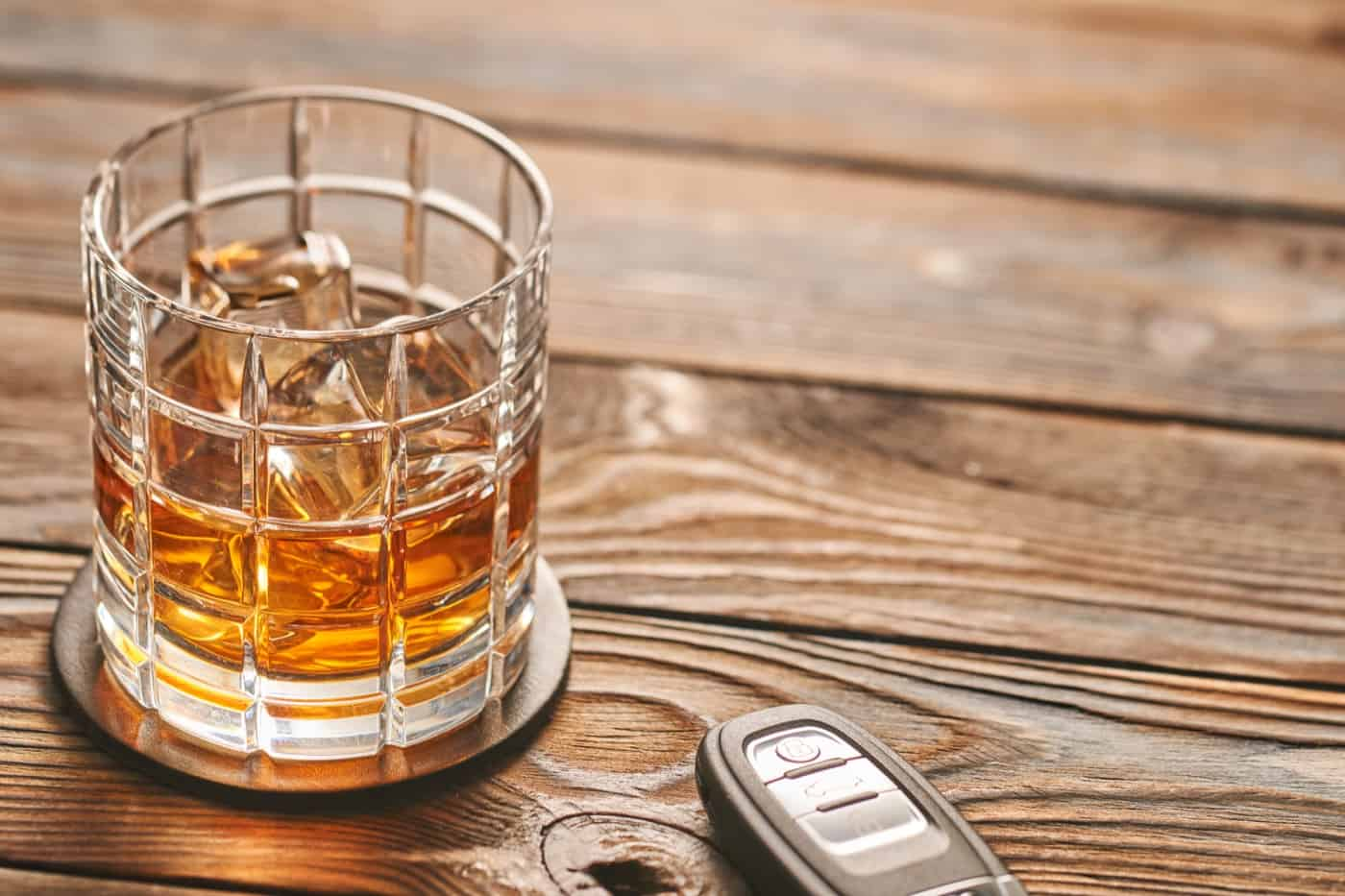 Glass of whiskey or alcohol drink with ice cubes and car key. Drink and drive concept.