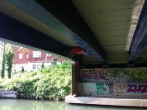 Dan, braced between two I-beams about 5 feet apart, underneath a bridge.