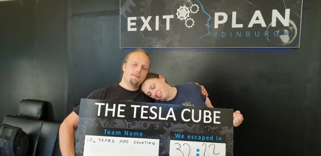 Dan and Ruth pretend to be asleep while holding a sign that says that they solved The Tesla Cube escape room in 32 mintues and 22 seconds.