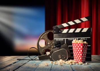 Retro film production accessories placed on wooden planks. Concept of film-making. Red curtain and movie screen on background; Shutterstock ID 594132752